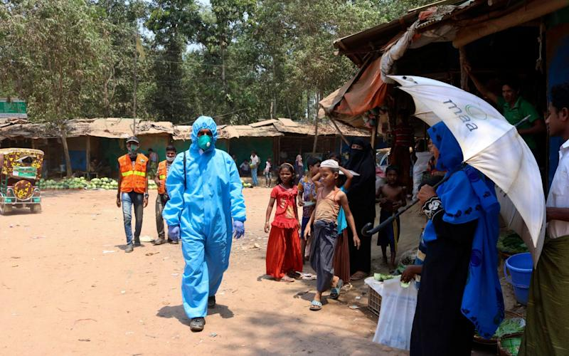 A health worker wearing a hazmat suit walks through the Cox's Bazar Rohingya camp, the largest refugee camp in the world -  Shafiqur Rahman/AP