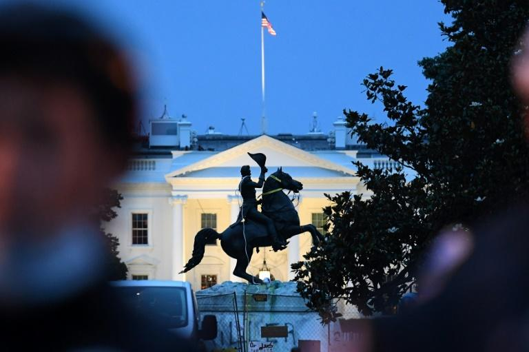Police officers guard the statue of former US President Andrew Jackson just outside the White House after protesters tried to topple it