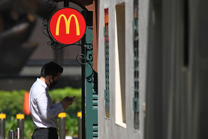 A man wearing face mask as a preventive measure against the spread of the COVID-19 coronavirus waits outside a McDonald's fast food outlet at Boat Quay next to the Raffles Place financial business district in Singapore on April 14, 2020. (Photo by ROSLAN RAHMAN / AFP) (Photo by ROSLAN RAHMAN/AFP via Getty Images)