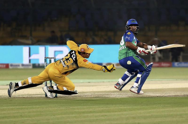 Zeeshan Ashraf of Multan Sultans who scores 50 off 35 balls, cuts a boundary as Peshawar Zalimi's Kamran Akmal looks on during the Pakistan Super League match at the National Stadium in Karachi, Pakistan, Friday, March 13, 2020. (AP Photo/Fareed Khan)