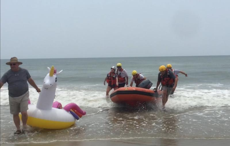 A man drags the unicorn to shore while the rescuers at Oak Island return to shore in the inflatable rescue boat.