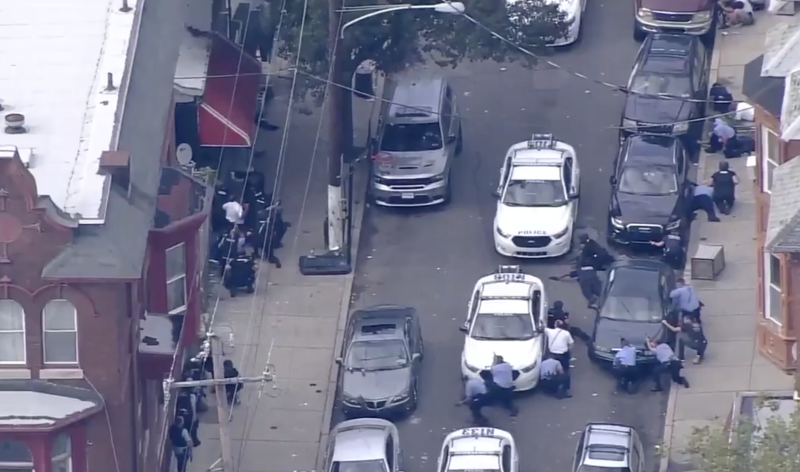Police surround a property with their guns drawn in Philadelphia.