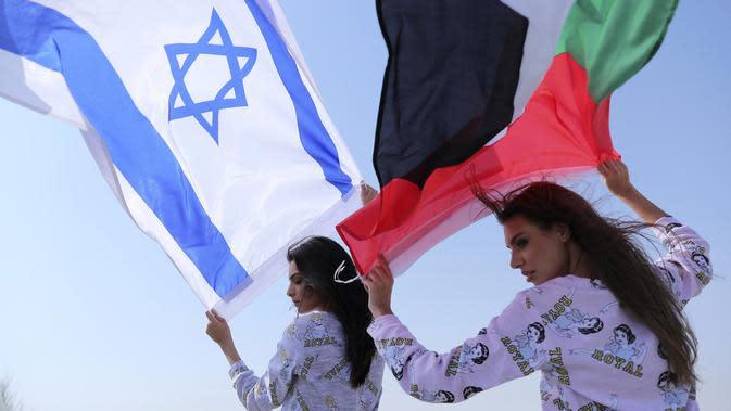 Model Israel May Tager (kiri) mengibarkan bendera Israel dan model Dubai asal Rusia Anastasia Bandarenka mengibarkan bendera Uni Emirat Arab saat pemotretan di Dubai, Uni Emirat Arab, 8 September 2020. Fix, merek pakaian dalam dan piyama Israel melakukan pemotretan di UEA. (AP Photo/Kamran Jebreili)