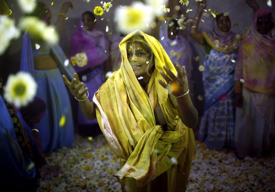 A widow throws flowers into the air during the Holi celebrations organised by non-governmental organisation Sulabh International at a widows' ashram in Vrindavan