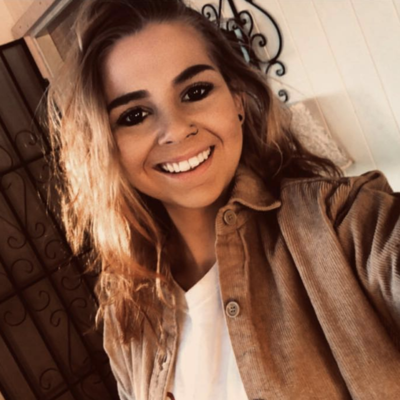 Caitlin Kirkaldy pictured in a beige jacket with a nose ring as she smiles into the camera for a selfie.