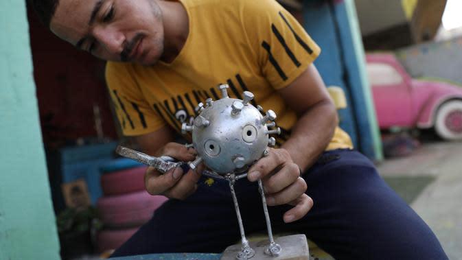 Ibrahim Salah mengerjakan sebuah patung di bengkel kerjanya di Giza, Mesir, pada 5 September 2020. Dua pemuda Mesir berhasil mengubah hobi mereka mendaur ulang barang bekas seperti besi tua menjadi berbagai dekorasi dan furnitur rumah sebagai sumber penghasilan yang stabil. (Xinhua/Ahmed Gomaa)