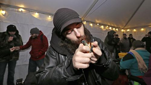 File-This Dec. 6, 2013, file photo shows Toby Tackett lighting a marijuana joint at a pot party at the Seattle Center, in Seattle. Colorado pot stores open Jan. 1 as retailers open their doors to the nation's first legal recreational pot industry. Sales in Washington, which also legalized recreational marijuana, are expected to start later in the year. (AP Photo/Elaine Thompson, File)