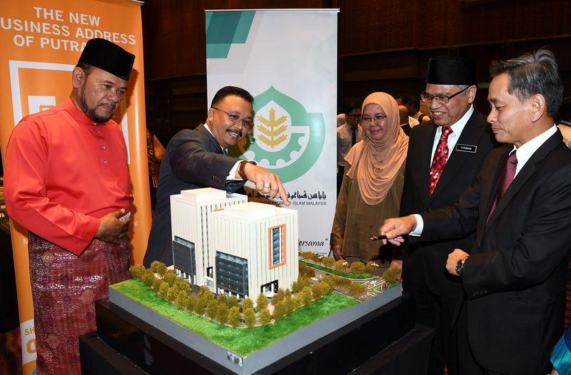 Yapeim director-general Datuk Abibullah Samsuddin (second left) looks at a model of the Ochre@Alamanda building after the Sale and Purchase Agreement ceremony, in Putrajaya December 7, 2017. — Bernama pic