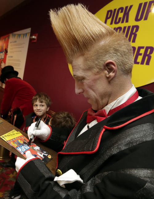 "This March 23, 2013 photo shows performer Bello Nock signing autographs in the lobby of the New Victory Theater, after his ""Bello Mania"" show, in New York. Nock, a seventh-generation circus performer, is never offstage during the 90-minute performance, which combines slapstick clowning with death-defying aerial stunts. He performs through March 31 at the New Victory before moving on to the Canadian side of Niagara Falls and then a 10-week stint at the Beau Rivage Casino in Biloxi, Miss. (AP Photo/Richard Drew)"