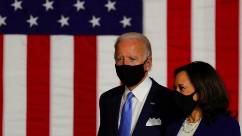 Joe Biden and Kamala Harris wearing masks in front of a Stars and Stripes flag