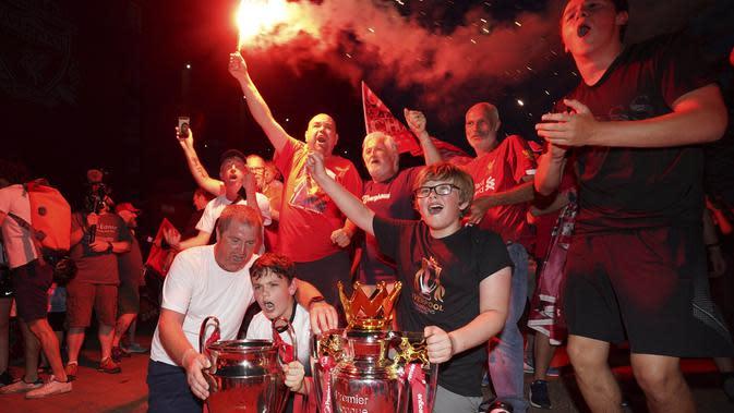 Suporter Liverpool merayakan gelar juara Premier League di depan Stadion Anfield, Kamis (25/6/2020). Titel juara Liga Inggris 2019-20 ini merupakan gelar pertama Liverpool setelah puasa selama 30 tahun. (AP/Jon Super)