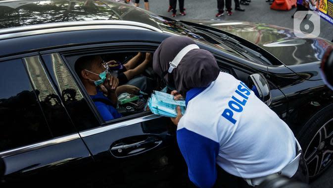 Petugas kepolisian membagikan masker saat sosialisasi pelaksanaan ganjil genap di Kawasan Bundaran HI, Jakarta, Minggu (2/8/2020). Ditlantas Polda Metro Jaya kembali memberlakukan sistem ganjil genap di 25 ruas jalan protokol DKI Jakarta mulai Senin, 3 Agustus 2020. (Liputan6.com/Faizal Fanani)