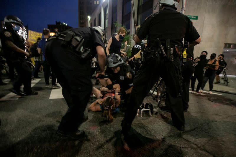 FILE PHOTO: Law enforcement officers detain a woman during a protest against the death in Minneapolis police custody of George Floyd, in Brooklyn, New York