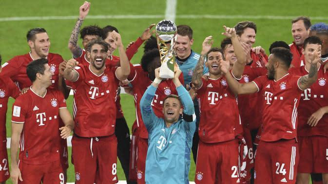Kiper Bayern Munchen, Manuel Neuer, mengangkat trofi juara Piala Super Jerman 2020 usai mengalahkan Borussia Dortmund di Allianz Arena, Kamis (1/10/2020) dini hari WIB. Bayern Munchen menang 3-2 atas Borussia Dortmund. (Andreas Gebert/Pool via AP)
