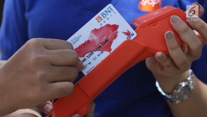 Pengunjung bertransaksi dengan tap cas BNI saat pertemuan tahunan IMF-Bank Dunia Grup di Bali, Jumat (11/12). PT BNI (Persero) Tbk menerbitkan 760 Kartu Virtual Account Debit yang diberikan kepada para delegasi negara peserta. (Liputan6.com/Angga Yuniar)