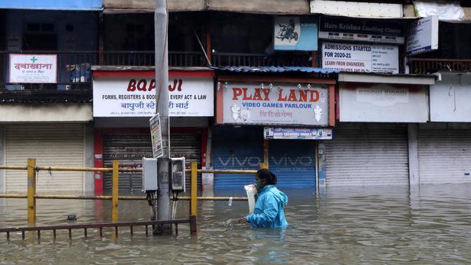 Seorang wanita berjalan melewati jalan yang tergenang air setelah hujan lebat di Mumbai, India, Rabu (23/9/2020). Musim hujan di India berlangsung dari Juni hingga September. (AP Photo/Rajanish Kakade)