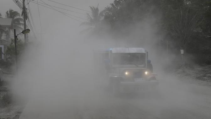 Sebuah jip melewati jalan yang tertutup abu vulkanik selama evakuasi saat gunung berapi Taal meletus di Lemery, provinsi Batangas, Filipina, Senin (13/11/2020). Erupsi gunung Taal memaksa puluhan ribu orang mengungsi serta membuat sekolah-sekolah dan toko di Manila tutup. (AP/Aaron Favila)