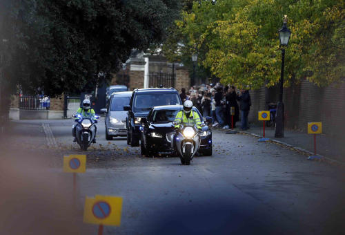 CAPTION ADDS THE DATE The car carrying Britain's Prince William, the Duchess of Cambridge and their son Prince George, is escorted by police as it drives from Kensington Palace, London, Wednesday, Oct. 23, 2013, on the way to St. James Palace for the christening of Prince George. Britain's 3-month-old future monarch, Prince George will be christened Wednesday with water from the River Jordan at a rare four-generation gathering of the royal family in London. (AP Photo/Lefteris Pitarakis)