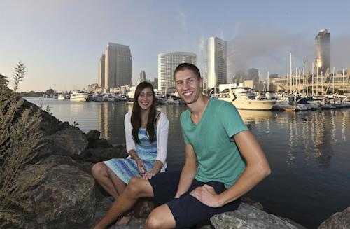 In this Tuesday, Oct. 15, 2013, photo, Melissa Grothues and her fiance John Steele pose at a spot on San Diego Bay in San Diego. The couple left the Buffalo, New York suburb of Amherst seeking a new life with a new environment and landed in San Diego. (AP Photo/Lenny Ignelzi)