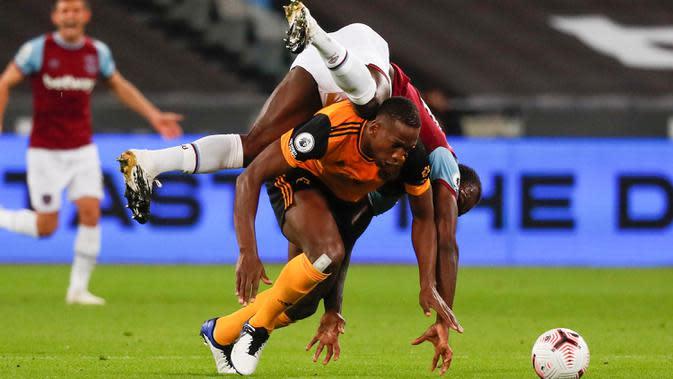 Gelandang West Ham, Michail Antonio jatuh di atas pemain Wolverhampton Wanderers Willy Boly dalam lanjutan Liga Inggris di London Stadium, Minggu (27/9/2020). West Ham United menang dengan skor telak 4–0 atas tamunya Wolverhampton Wanderers. (Frank Augstein/Pool via AP)
