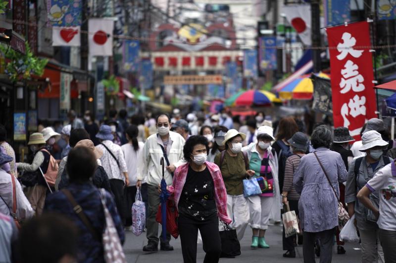 Shoppers walking in a street in Tokyo on 24 June, 2020. (PHOTO: AP)