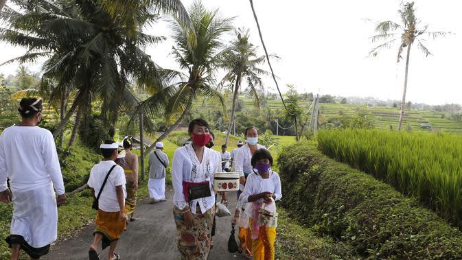Orang-orang yang memakai masker wajah sebagai pencegahan terhadap wabah virus Corona berjalan ke sebuah pura di sebuah desa di Bali, Senin (21/9/2020). (AP Photo / Firdia Lisnawati)