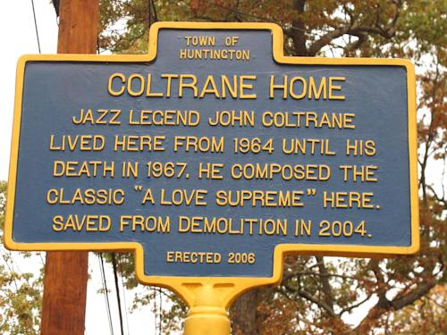 This Wednesday, Oct. 23, 2013 photo shows a historical marker outside the Dix Hills, N.Y. home of jazz legend John Coltrane. The move to restore the home began about a decade earlier when local jazz enthusiast Steve Fulgoni learned a developer had purchased the property with plans to demolish the home and build three smaller houses. He organized a lobbying effort to save the home, and eventually Huntington town officials purchased the property from the developer for $975,000 and designated it as a town park. (AP Photo/Frank Eltman)