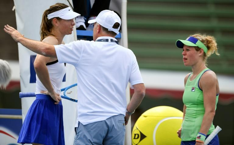 Maria Sharapova (left) and Laura Siegemund speak to a Kooyong Classic official before their match was abandoned in smoke haze on Tuesday
