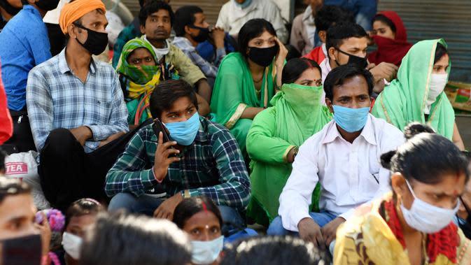 Pekerja migran yang terdampar dan keluarga mereka berkumpul menunggu pemeriksaan medis sebelum pergi dengan kereta api untuk kembali ke kota asal mereka ke Jaunpur, negara bagian Uttar Pradesh, setelah pemerintah melonggarkan lockdown di Amritsar, India, Selasa (19/5/2020). (NARINDER NANU/AFP)