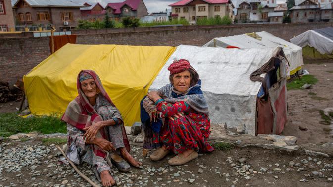 Gowri Khan dan Khatija, perempuan pengembara Kashmir Bakarwal duduk di luar kamp sementara di pinggiran Srinagar, India, 31 Agustus 2020. Suku Bakarwals adalah kaum penggembala nomaden di Jammu Kashmir, yang berpindah-pindah mencari padang rumput yang baik untuk ternak mereka. (AP Photo/Dar Yasin)