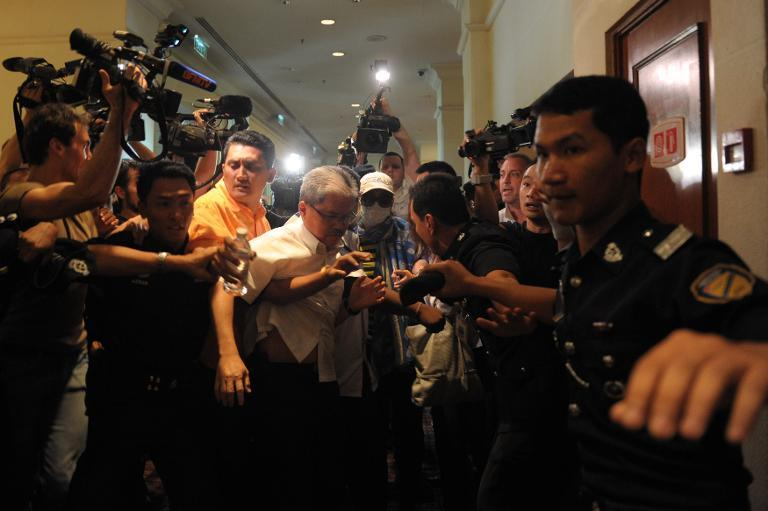A Chinese relative of passengers from the missing Malaysia Airlines flight is stopped and escorted away by Malaysian police from entering the media centre before the start of a press conference at a hotel near Kuala Lumpur airport on March 19, 2014