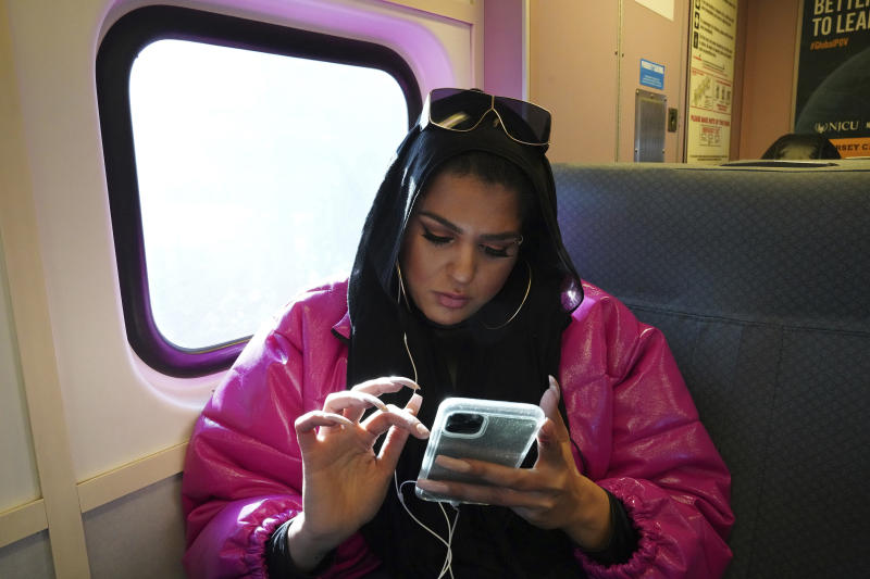 In this Dec. 20, 2019, photo, Amani Al-Khatahtbeh, founder of MuslimGirl.com, sits for an interview inside her family's video game and electronic store business in Somerville, N.J. Al-Khatahtbeh started the website as a way to defy Muslim stereotypes after 9/11. A decade later, Al-Khatahtbehhas built it into an online magazine with a global audience. (AP Photo/Emily Leshner)