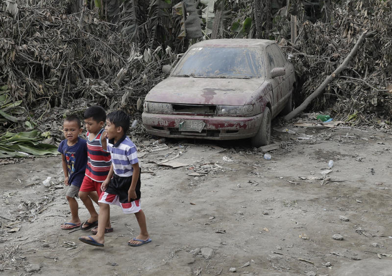 """Boys pass by a car that is covered in volcanic-ash at a town near Taal volcano in Tagaytay, Cavite province, southern Philippines on Sunday Jan. 19, 2020. Philippine officials said Sunday the government will no longer allow villagers to return to a crater-studded island where an erupting Taal volcano lies, warning that living there would be """"like having a gun pointed at you."""" (AP Photo/Aaron Favila)"""