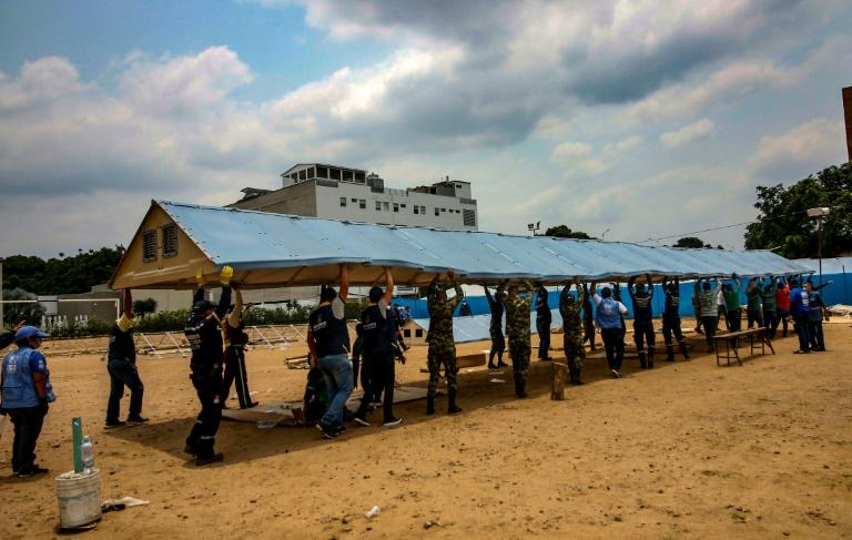 Firefighters, soldiers and workers from the office of the United Nations High Commissioner for Refugees (UNHCR)setting up a field hospital for coronavirus cases on the border with Venezuela, on March 28, 2020