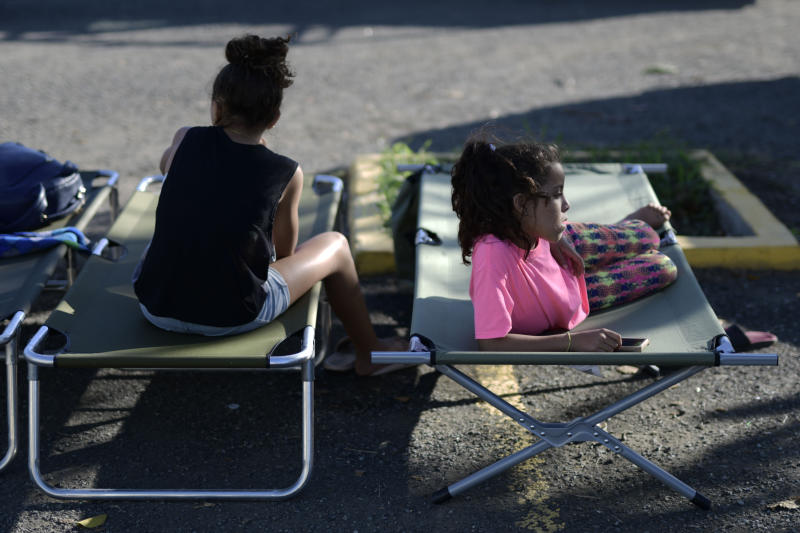 Neighbors rest outside a shelter afraid of aftershocks, after an earthquake in Guanica, Puerto Rico, Tuesday, Jan. 7, 2020. A 6.4-magnitude earthquake struck Puerto Rico before dawn on Tuesday, killing one man, injuring others and collapsing buildings in the southern part of the island. (AP Photo/Carlos Giusti)
