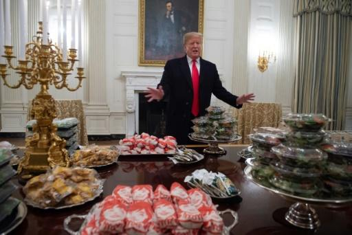 Trump, an unapolegetic lover of fast food, shows off burgers bought for the 2018 College Football Playoff National Champion Clemson Tigers at the White House on January 14, 2019