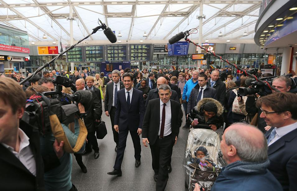 Labour Party leader Ed Miliband, centre left, arrives at Manchester Piccadilly station before boarding the party's General Election battle bus in Manchester England  Tuesday March 31, 2015. Britain with hold a parliamentary election on Thursday May 7, 2015.  (AP Photo/Dave Thompson/PA) UNITED KINGDOM OUT
