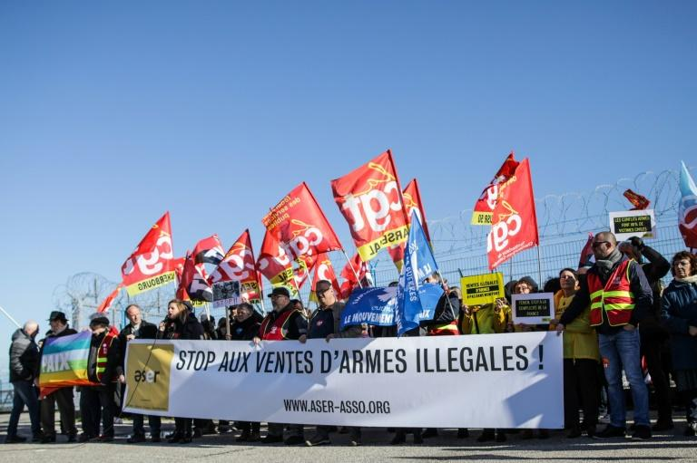"People hold a banner reading ""Stop the sale of illegal weapons"" during a demonstration at Cherbourg harbor"