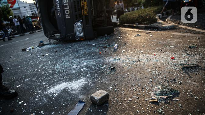 Batu berserakan dekat sebuah mobil polisi yang dirusak massa saat bentrok di kawasan Pejompongan, Jakarta, Rabu (7/10/2020). (Liputan6.com/Faizal Fanani)