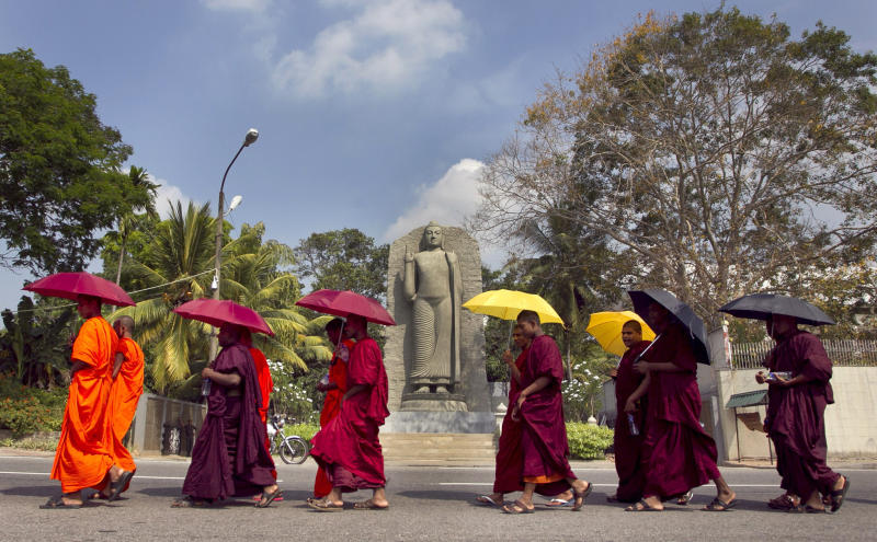 FILE - In this March 4, 2014, file photo, Sri Lankan Buddhist monks walk towards the U.N. office in Colombo, Sri Lanka. The Indian Ocean island nation of Sri Lanka, which will elect a new president on Saturday, Nov. 16, 2019 has had a tumultuous history. Since gaining independence from British colonial rule in 1948, the country has seen three major armed conflicts in which hundreds of thousands have died. It also has had its share of natural disasters. As it prepares to elect its seventh president, Sri Lanka remains a divided nation, with ethnic, political and economic issues unresolved. (AP Photo/Eranga Jayawardena, File)