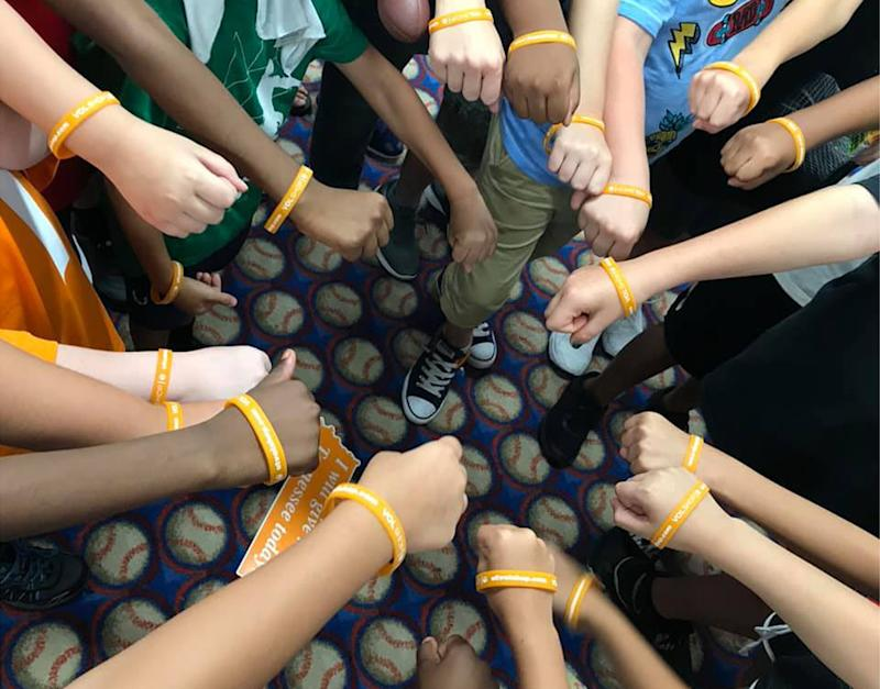 The boy's classmates show off their University of Tennessee wrist bands received in a care package from the college. Source: Facebook / Laura Snyder