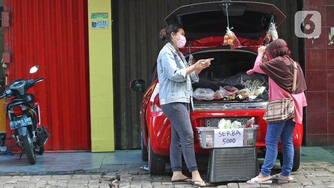 Cynthia (28) mahasiswi perguruan tinggi swasta (kiri) melayani calon pembeli di Jalan Santosa, Depok, Jawa Barat, Kamis (21/5/2020). Cynthia menggunakan mobil pribadinya sebagai lapak berjualan berbagai macam sayuran dengan harga serba Rp 5.000. (Liputan6.com/Herman Zakharia)