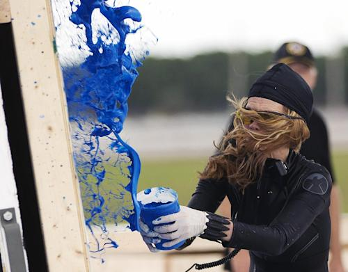 Princess Tarinan von Anhalt works on one of her paintings Tuesday, April 30, 2013 on the West Palm Beach, Fla. airport tarmac. Princess Tarinan von Anhalt's creative process involves hurling paint into a Learjet engine, splattering the colors onto a canvas to create the abstract designs for which she has become known. Tuesday's demonstration is part of an event by a private jet services company and an art group to celebrate the 50th anniversary of Learjet. (AP Photo/J Pat Carter)