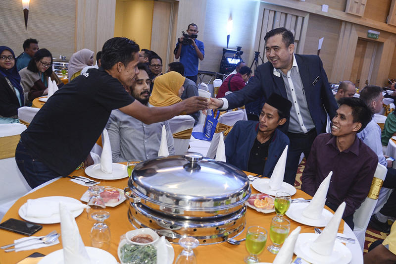 Anthony Loke greets guests during a breaking of fast gathering at the Transport Ministry in Putrajaya May 15, 2019. — Picture by Miera Zulyana