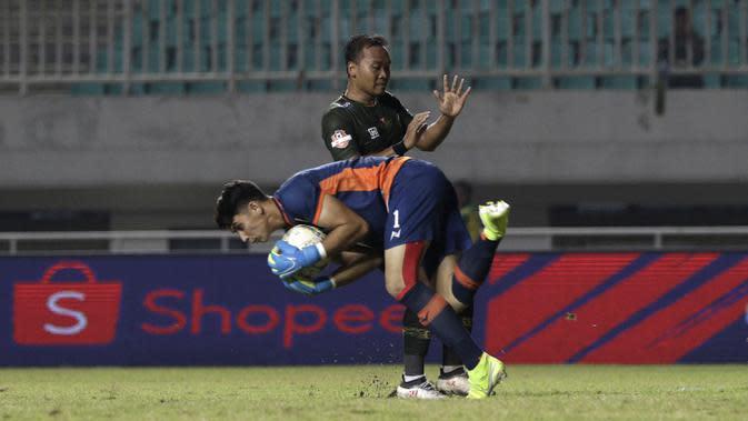 Kiper Borneo FC, Nadeo Winata, berduel dengan geladang Tira Persikabo, Wawan Febriyanto, pada laga Shopee Liga 1 di Stadion Pakansari, Bogor, Minggu (1/9). Borneo tahan imbang 2-2 Tira Persikabo. (Bola.com/Yoppy Renato)