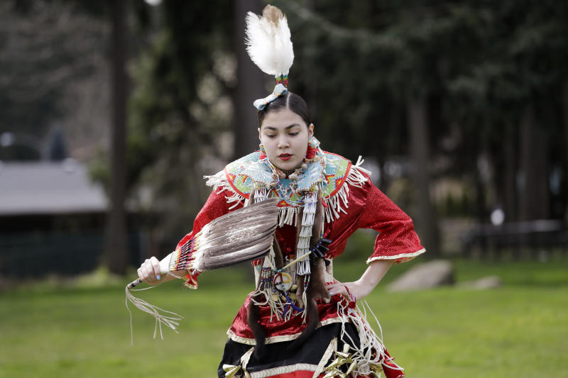 In this photo taken Saturday, April 4, 2020, Wicahpi Cuny, 14, a Dakota and Lakota tribal member, dances during a live streamed powwow from a park near her home, in Puyallup, Wash. The largest powwows in the country have been canceled or postponed amid the spread of the coronavirus. Tribal members have found a new outlet online with the Social Distance Powwow. They're sharing videos of colorful displays of culture and tradition that are at their essence meant to uplift people during difficult times. (AP Photo/Elaine Thompson)