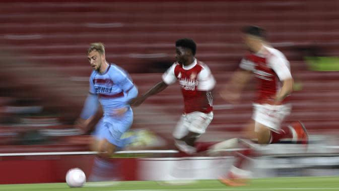 Penyerang West Ham, Jarrod Bowen membawa bola dari kejaran gelandang Arsenal, Bukayo Saka pada pertandingan lanjutan Liga Inggris di Stadion Emirates di London, Inggris, Sabtu (19/9/2020). Arsenal menang tipis 2-1 atas West Ham. (AP Photo/Ian Walton, Pool)