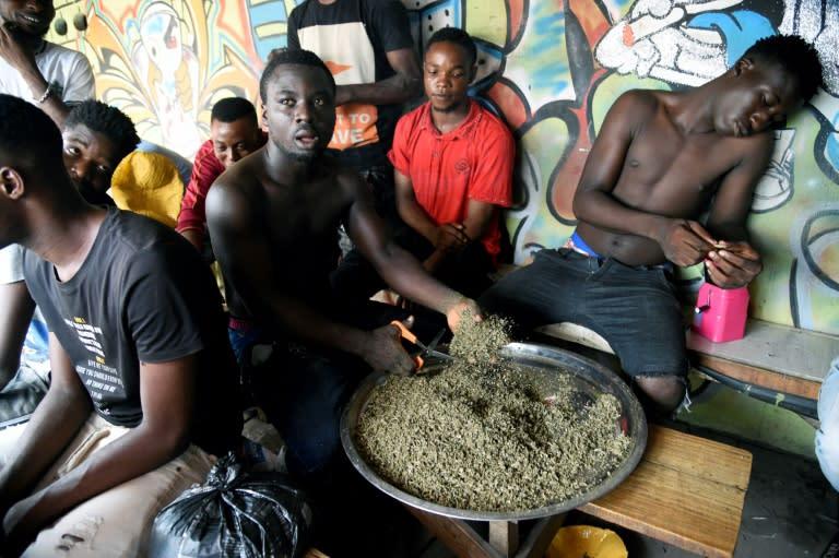 A vendor cuts marijuana for sale in Lagos