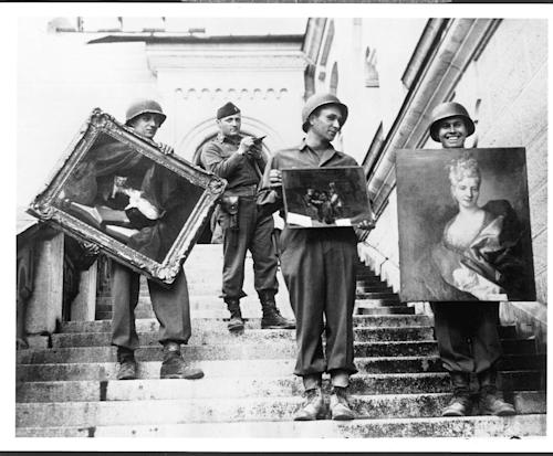 This photo provided by The Monuments Men Foundation for the Preservation of Art of Dallas, shows Monuments Man James Rorimer, with notepad, as he supervises American GI's hand-carrying paintings down the steps of the castle in Neuschwanstein, Germany in May of 1945. From a fairy tale-inspiring castle in the Bavarian Alps to a serene sculpture of Mary and Jesus by Michelangelo tucked away in a church in Belgium, sites and works of art across Europe can give travelers a glimpse at the heroic work done by those who worked to save cultural treasures during World War II.(AP Photo/National Archives and Records Administration)