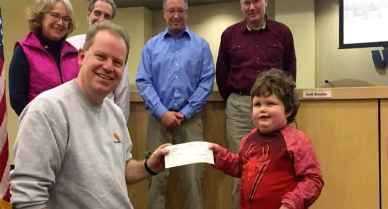 Quinn Larson receiving a cheque to kick-start funding for the playground.